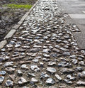 Old worn cobblestone edging around flagstones in a low angle view showing the texture of the stones Royalty Free Stock Photography