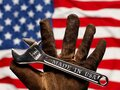 Old worn work glove holding adjustable wrench with Made in USA text. American workforce or industry, or America labor Royalty Free Stock Photo