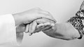 Old wrinkled hand a young touches and holds an black and white Stock Photo