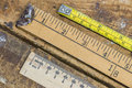 Old yard stick, ruler and tape measure on scratched workshop tab Royalty Free Stock Photo