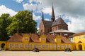 Old yellow building in front of roskilde cathedral domkirke denmark is the burial site for the royal family since it has been Stock Photos