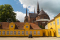 Old yellow building in front of roskilde cathedral domkirke denmark is the burial site for the royal family since it has been Stock Photography
