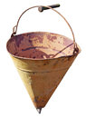 The old yellow hollow fire triangle bucket hangs on the nail. Royalty Free Stock Photo