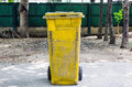 Old yellow recycling bin on concrete Royalty Free Stock Images