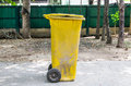 Old yellow recycling bin on concrete Stock Photos