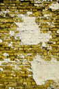 Old yellow wall with cracks and patches of plaster Stock Photo