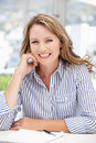 Older career woman sat at desk smiling Royalty Free Stock Photo