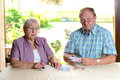 Older couple calculating her budget men and women money Royalty Free Stock Photo