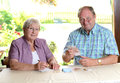 Older couple calculating her budget men and women money Royalty Free Stock Images