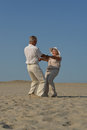 Older couple in love walking barefoot the sand Stock Images