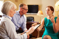 Older couple talking to financial advisor in office looking at document Royalty Free Stock Images