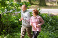 Older couple wearing sportswear and running in forest at mountai Royalty Free Stock Photo
