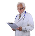Older experienced doctor with gray hair and eyeglasses wearing a lab coat and stethoscope holding a chart Royalty Free Stock Photo