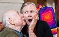 Older gentleman kissing older woman on cheek shocked women in livingroom Stock Photo