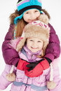 Older girl embraces her younger sister from behind standing on snow background Royalty Free Stock Photography