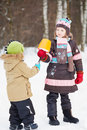 Older girl gives eskimo to younger child in winter park made of snow plastic bucket and broken branch Stock Photography