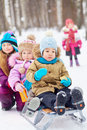 Older girl pushes sled with two little children first asian boy eats cracker another one stands behind not in focus Royalty Free Stock Photo