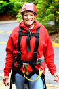 Older lady wearing zipline gear a brave senior citizen with red coat all ready for and zip line and helmet shallow depth of field Royalty Free Stock Photography