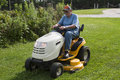 Older Male Mowing Grass With His Riding Mower