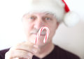 Older man with candy cane in santa hat offers a Royalty Free Stock Photos