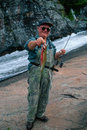 Older man holding a nice trout he just caught vertical portrait of an yellowstone cutthroat that out of high mountain stream the Stock Photography