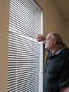 Older man looking out window blinds. Royalty Free Stock Photo