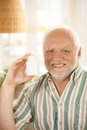 Older man presenting medication smiling holding up phial looking at camera copy space Stock Photos