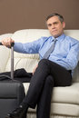 Older man sitting on couch with luggage. Royalty Free Stock Photo