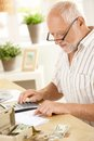 Older man using calculator at home concentrating on financial job Royalty Free Stock Photography