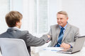 Older man and young man shaking hands in office business technology concept men men Stock Images