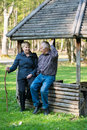 Older people sitting in the arbor on forest and speaking together Stock Images