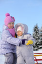 Older sister hugs baby dressed in warm clothes outdoor at winter Stock Images