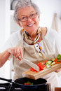 Older woman cooking in a kitchen Royalty Free Stock Photos