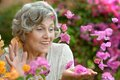 Older woman with flowers close up portrait of an on walk pink Royalty Free Stock Photos