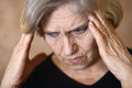 Older woman with a headache portrait of an on beige background Royalty Free Stock Photos