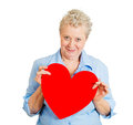 Older woman in love closeup portrait of senior mature happy joyful female holding red valentine heart looking at you isolated on Royalty Free Stock Image