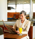 Older woman reading newspaper in a cafe Royalty Free Stock Photography