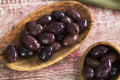 Olive appetizers wooden bowl and scoop of kalamata olives Royalty Free Stock Image