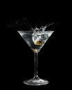 Olive dropped in a cocktail glass with liquid making big splash isolated on black Royalty Free Stock Images