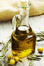 Olive oil bottle with leaves and fresh green olives Royalty Free Stock Images
