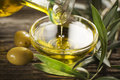 Olive oil bottle pouring virgin in a bowl close up Royalty Free Stock Photos
