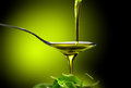 Olive oil dop poured into spoon Stock Images