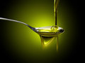 Olive oil dop poured into spoon Royalty Free Stock Images