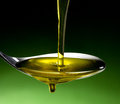 Olive oil dop poured into spoon Royalty Free Stock Photos