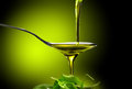 Olive oil dop poured into spoon Royalty Free Stock Photo