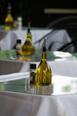 Olive oil in an italian restaurant bottles of amber sit on glass topped tables Stock Photo