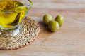 Olive oil jug and olives on the cutting desk Royalty Free Stock Photo