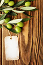 Olive oil label olives over wooden background and Royalty Free Stock Image