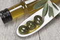 Olive oil and olives on a wooden surface Stock Images