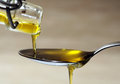 Olive oil over spoon extra virgin pouring from bottle to closeup Royalty Free Stock Photography